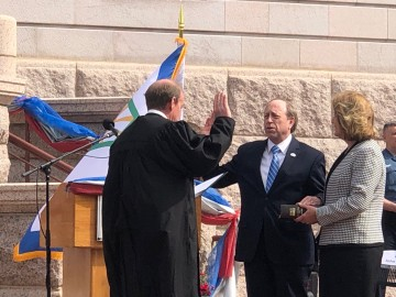 Mayor John Suthers and his wife Janet stand before Municipal Court Judge Kane. Suthers stands with his right hand raised and his left hand on a family Bible held by Janet.