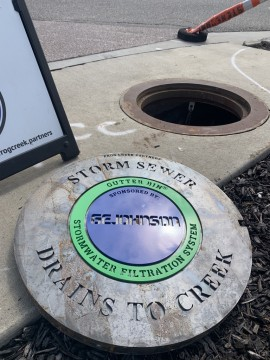 """Lid to new storm drain where gutter bin is being installed. The words """"storm sewer drains into creek. Gutter bin stormwater filtration system  sponsored by GE Johnson"""" is engraved on the lid."""