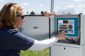 woman adjusting settings in irrigation smart control box. The box is outside. A green grassy field is in the background.