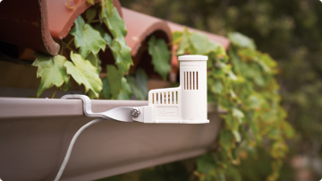 A small, white device to collect and measure rainfall hangs from a rain gutter.