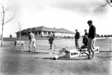 Old photo of golfers playing at Patty Jewett with the clubhouse in the background.