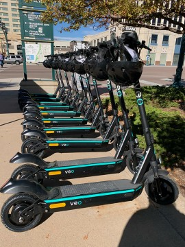 line of pared scooters with helmet on handlebars