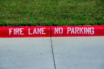 A curb painted red with the words 'fire lane no parking'