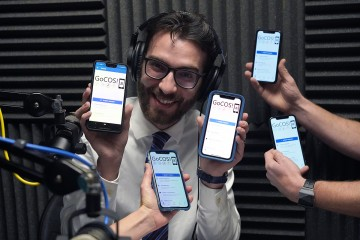 Ted Skroback surrounded by phones showing the GoCOS! app