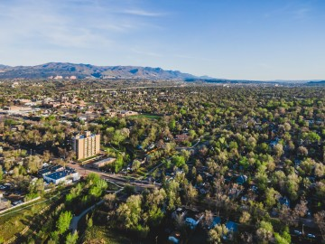 aerial view of trees across Colorado Springs with mountains in the background.