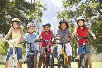 Group of girls on bicycles wearing helmets