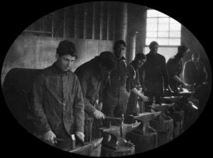 A line of blacksmiths working in a blacksmith shop