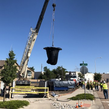 crane lifting net over dumpster
