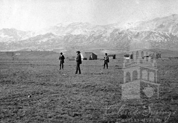 Title: Surveying Colorado Springs, 1871. From the CSPM Collection. Description: three men standing in a open prairie at the base of Pikes Peak.