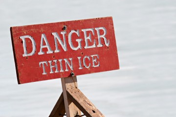 """a sign on the ice reads """"danger: thing ice"""""""