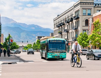 busy downtown street with pedestrians, bike commuters, bus, and personal vehicles