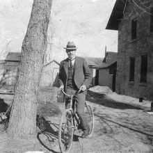 man standing astride a bike with a large tree and brick buildings around him.