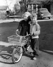 small boy stands next to a small girl on a bike. House with a VW bug in the driveway in the background.