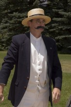 Actor dressed as General Palmer wearing a straw hat, round glasses and a handle bar mustache
