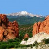 a snow capped pikes Peak with the red rocks of Garden of the Gods in the foreground