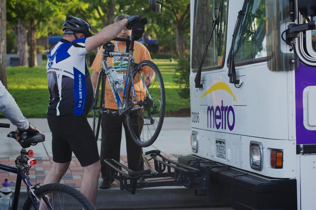 person loading their bike onto a bus