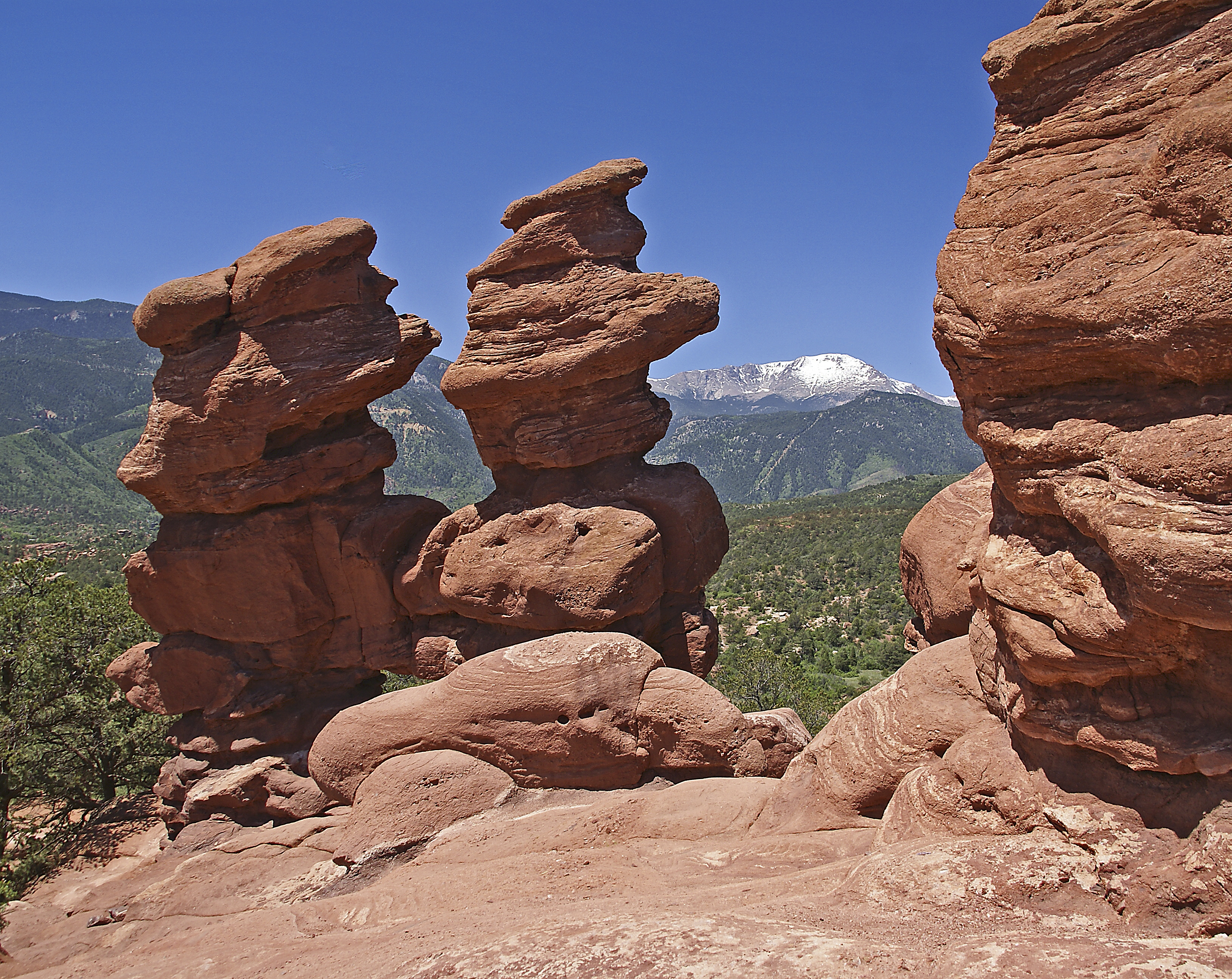 Pikes Peak is seen behind the Siamese Twins red rock formations at Garden of the Gods Park